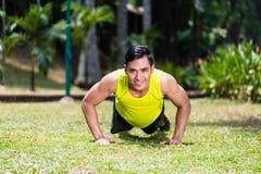 做体育俯卧撑的坚强的亚裔人在公园 库存图片