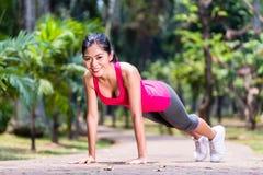 做体育俯卧撑的坚强的亚裔妇女在公园 免版税图库摄影