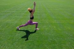 做体育的一双黑T恤杉、桃红色裤子和运动鞋的一个年轻非裔美国人的女孩在绿草行使和 库存图片