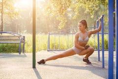 做体育的俏丽的妇女舒展锻炼在室外的夏天 免版税库存照片