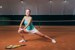 做体育的快乐的妇女在室内网球场行使 免版税库存照片