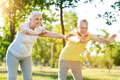 做体育的快乐的资深夫妇一起行使 免版税库存图片