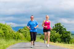 做体育的愉快的夫妇跑步在农村街道上 库存照片