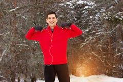 做体育锻炼和听的音乐的红色毛线衣的英俊的微笑的运动员 室外的活动 免版税图库摄影