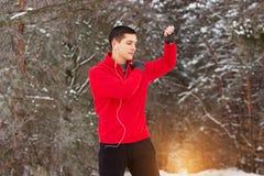 做体育锻炼和听的音乐的红色毛线衣的年轻和英俊的运动员 室外的活动 免版税库存照片
