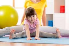 做体育锻炼的母亲和女儿孩子 弯曲在舒展的孩子用手下难倒 免版税库存图片