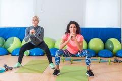 做体重的运动服的两名妇女蹲,当训练户内在体育馆时 免版税库存照片