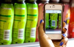 做使用智能手机的超级市场商店 库存照片