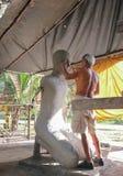 做修士雕塑的年长艺术家雕刻家在寺庙 库存照片