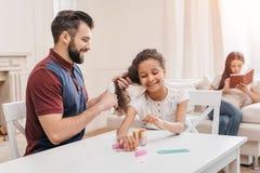 做修指甲的女儿,当梳她的头发时的父亲 库存图片