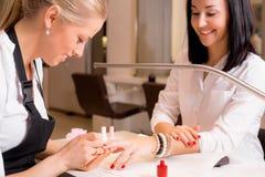 做修指甲的愉快的妇女 免版税图库摄影