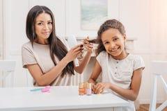 做修指甲的非裔美国人的女儿,当梳她的头发时的母亲 库存图片