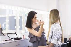 做修改的年轻化妆师对俏丽的模型 免版税图库摄影