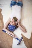 做修理的年轻美丽的妇女在有工具的房子里 库存照片