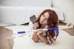 做修理的年轻美丽的妇女在有工具的房子里 库存图片