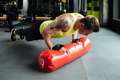 做俯卧撑和使用沙袋的年轻坚强的运动员 库存照片