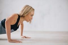 做俯卧撑或新闻的年轻愉快的可爱的妇女特写镜头上升锻炼 免版税图库摄影