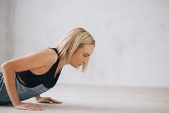 做俯卧撑或新闻的年轻愉快的可爱的妇女特写镜头上升锻炼 免版税库存图片