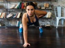 做俯卧撑的一方面年轻健身妇女在地板上行使 免版税库存图片