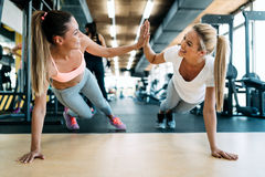 做俯卧撑的两个可爱的健身女孩 图库摄影
