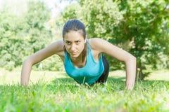 做俯卧撑的健身妇女 免版税库存图片