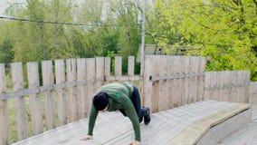 做俯卧撑的坚强的年轻人 做男性运动员运动员锻炼训练户外的夏天增加锻炼 股票录像