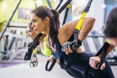 做俯卧撑的妇女训练有trx的胳膊 免版税库存图片