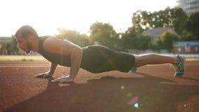 做俯卧撑的有胡子的肌肉人,男性运动员行使增加晴朗的户外,体育场的 健康生活方式 影视素材