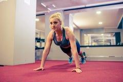 做俯卧撑的白肤金发的女孩在健身房早晨 免版税库存照片