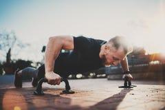做俯卧撑的英俊的年轻体育人在公园在晴朗的早晨 概念健康生活方式 户外培训 图库摄影
