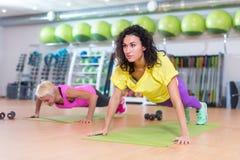 做俯卧撑的运动服的适合的妇女在席子行使户内在健身房 免版税库存照片