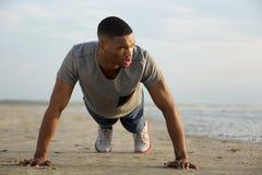 做俯卧撑的年轻人在海滩 免版税图库摄影
