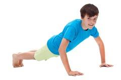 做俯卧撑的年轻男孩 库存照片