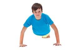 做俯卧撑-正面图的年轻男孩 免版税图库摄影