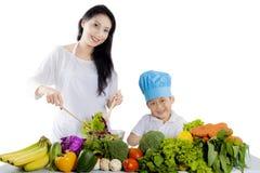 做健康沙拉的儿子和母亲 图库摄影