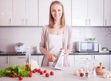 做健康食物的妇女在厨房里 免版税库存照片