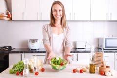 做健康食物的微笑的妇女 免版税库存照片