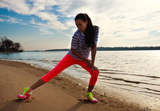 做健身和瑜伽锻炼的少妇在沙子靠岸 图库摄影