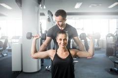 做健身在个人教练员帮助下的妇女 库存图片
