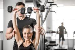 做健身在个人教练员帮助下的妇女 免版税库存图片