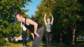 做健身的两年轻女人在有他们的教练员的公园在明亮的好日子-做在脊椎的锻炼- 影视素材