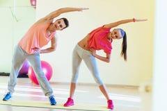做健身的健身房的两青年人锻炼 库存照片