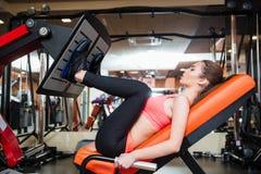 做健身的坚强的女运动员为在健身房的腿肌肉行使 库存照片