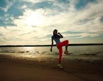 做健身的少妇在沙子海滩行使 库存图片
