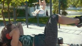 做健身的少妇在酒吧拔的肌肉人前面行使户外晴天 影视素材