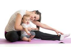 做健身的少妇母亲行使与婴孩,在白色背景隔绝的演播室画象 免版税库存照片