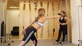 做健身的少妇 做在她的手上的妇女力量锻炼在健身房 观看她的另一名妇女 股票视频