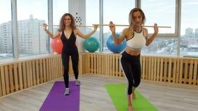 做健身的年轻微笑的妇女 拿着棍子的Squating 股票视频