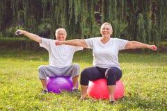 做健身的成熟夫妇在健身球行使在公园 库存图片