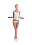 做健身的白色女用贴身内衣裤的一名年轻和亭亭玉立的白肤金发的妇女 免版税库存照片